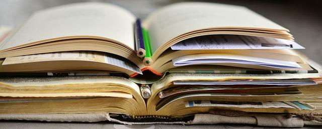 três livros abertos, separados por canetas e marca-textos